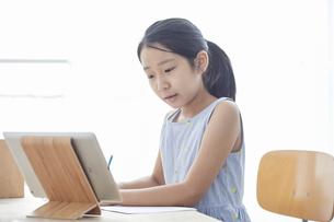 タブレットPCで勉強する小学生の女の子の写真素材 [FYI04570947]