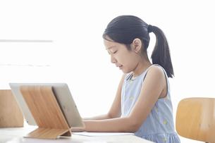 タブレットPCで勉強する小学生の女の子の写真素材 [FYI04570948]