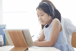 タブレットPCで勉強するヘッドセットをつけた小学生の女の子と大人の写真素材 [FYI04570949]