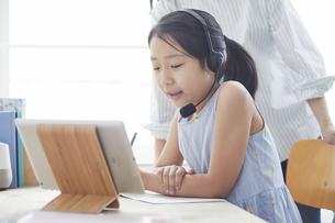 タブレットPCで勉強するヘッドセットをつけた小学生の女の子と大人の写真素材 [FYI04570950]