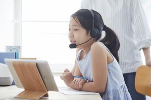 タブレットPCで勉強するヘッドセットをつけた小学生の女の子と大人の写真素材 [FYI04570952]