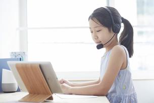 タブレットPCで勉強するヘッドセットをつけた小学生の女の子の写真素材 [FYI04570954]