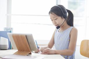 タブレットPCで勉強するヘッドセットをつけた小学生の女の子の写真素材 [FYI04570955]