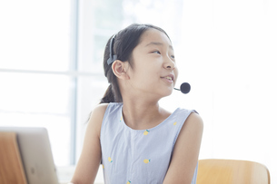 タブレットPCで勉強するインカムをつけた小学生の女の子の写真素材 [FYI04570960]