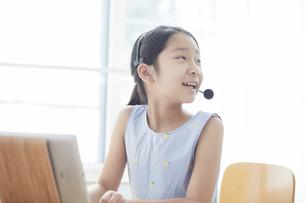 タブレットPCで勉強するインカムをつけた小学生の女の子の写真素材 [FYI04570961]