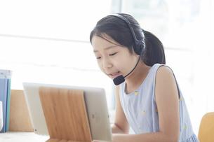 タブレットPCで勉強するインカムをつけた小学生の女の子の写真素材 [FYI04570962]