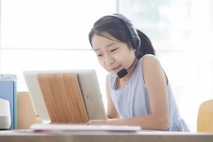 タブレットPCで勉強するインカムをつけた小学生の女の子の写真素材 [FYI04570964]