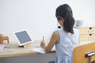 タブレットPCで勉強するインカムをつけた小学生の女の子の写真素材 [FYI04570965]