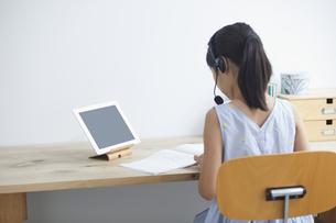 タブレットPCで勉強するインカムをつけた小学生の女の子の写真素材 [FYI04570966]