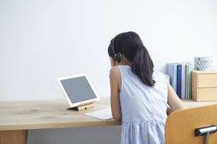 タブレットPCで勉強するインカムをつけた小学生の女の子の写真素材 [FYI04570967]