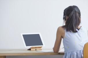 タブレットPCで勉強するインカムをつけた小学生の女の子の写真素材 [FYI04570970]