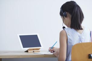 タブレットPCで勉強するインカムをつけた小学生の女の子の写真素材 [FYI04570971]