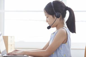 ノートパソコンで勉強するインカムをつけた小学生の女の子の写真素材 [FYI04570973]