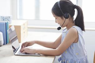 ノートパソコンで勉強するインカムをつけた小学生の女の子の写真素材 [FYI04570974]