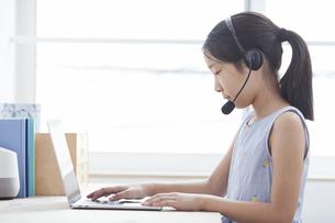 ノートパソコンで勉強するインカムをつけた小学生の女の子の写真素材 [FYI04570976]