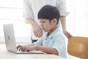 ノートパソコンで勉強する小学生の男の子と大人の写真素材 [FYI04570986]