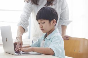 ノートパソコンで勉強する小学生の男の子と大人の写真素材 [FYI04570987]