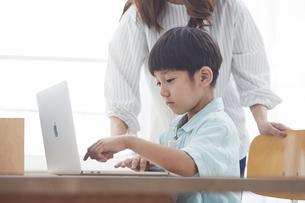 ノートパソコンで勉強する小学生の男の子と大人の写真素材 [FYI04570989]