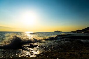 海岸へ打ち付ける波と海の向こうに見える江ノ島の写真素材 [FYI04570999]