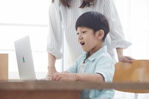 ノートバソコンで勉強する小学生の男の子と見守る女性の写真素材 [FYI04571084]