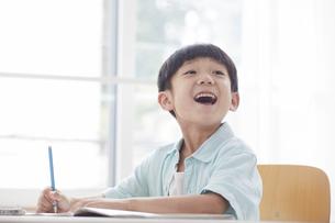 勉強する笑顔の小学生の男の子の写真素材 [FYI04571096]