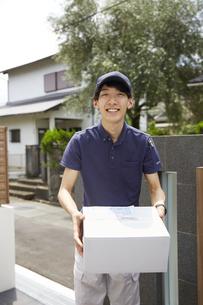 荷物を運んでいる宅配員の写真素材 [FYI04573691]