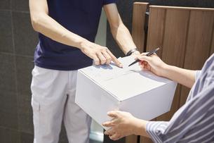 荷物の受け渡しをする宅配員の写真素材 [FYI04573711]