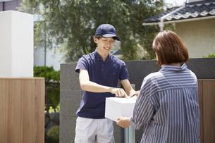 荷物の受け渡しをする宅配員の写真素材 [FYI04573712]