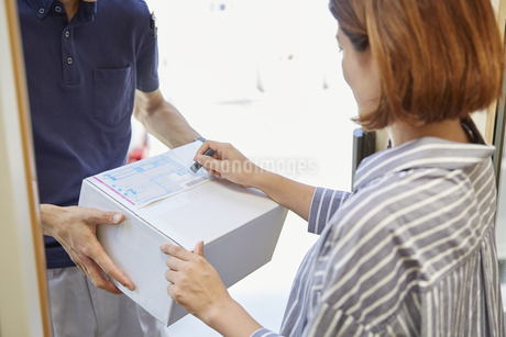 荷物の受け渡しをする宅配員の写真素材 [FYI04573717]