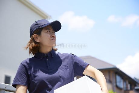 荷物を運んでいる宅配員の女性の写真素材 [FYI04573722]