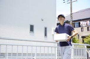 荷物を運んでいる宅配員の男性の写真素材 [FYI04573726]