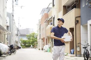 荷物を運んでいる宅配員の男性の写真素材 [FYI04573737]