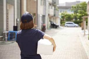 荷物を運んでいる宅配員の女性の写真素材 [FYI04573741]