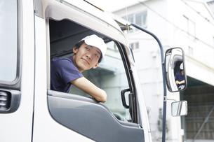 トラックに乗っている宅配員の男性の写真素材 [FYI04573744]