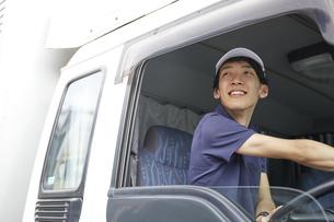 トラックに乗っている宅配員の男性の写真素材 [FYI04573746]