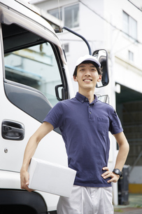 トラックの前に立っている宅配員の男性の写真素材 [FYI04573747]