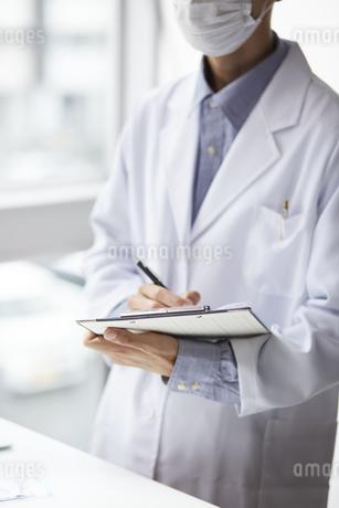 バインダーの書類に書き込むペンを持った白衣の男性の写真素材 [FYI04573749]