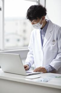 ノートパソコンに向かって入力している白衣の男性の写真素材 [FYI04573751]