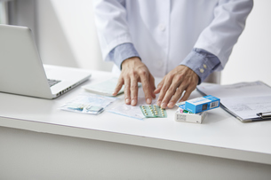 カウンターの上で薬を確認している白衣の男性の手元の写真素材 [FYI04573752]