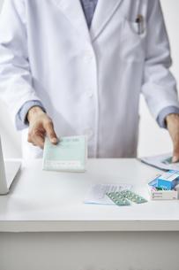 カウンターでお薬手帳を差し出している白衣の男性の手元の写真素材 [FYI04573753]