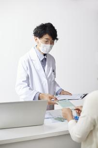 カウンター越しにお薬手帳を手渡す白衣の男性の写真素材 [FYI04573757]