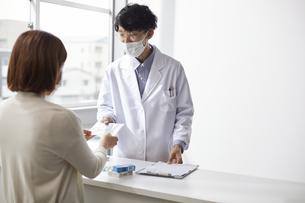カウンター越しに薬を手渡す白衣の男性と後ろ姿の女性の写真素材 [FYI04573758]
