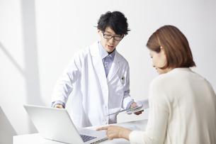 カウンター越しにノートパソコンを見ながら説明をしている白衣の男性と後ろ姿の女性の写真素材 [FYI04573759]