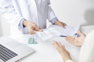 薬を渡している白衣の男性の手元とそれを受け取る女性の手元の写真素材 [FYI04573760]