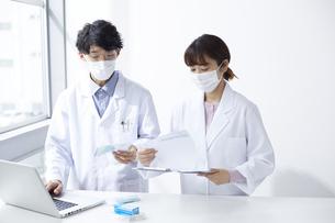 ノートパソコンを見ながら薬の確認している白衣を着た男女の写真素材 [FYI04573762]