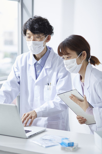 ノートパソコンを見ながら薬の確認している白衣を着た男女の写真素材 [FYI04573763]