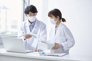 ノートパソコンを見ながら薬の確認している白衣を着た男女の写真素材 [FYI04573764]