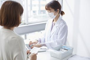 薬の説明をしている白衣の女性と後ろ姿の女性の写真素材 [FYI04573769]
