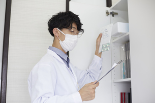 バインダーを持ち棚から薬を出している白衣の男性の写真素材 [FYI04573773]