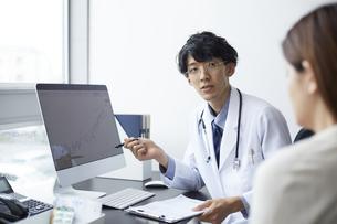 パソコンのモニターを前に説明する白衣の男性の写真素材 [FYI04573783]